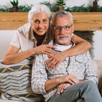 Retrato de los pares mayores cariñosos que miran la cámara