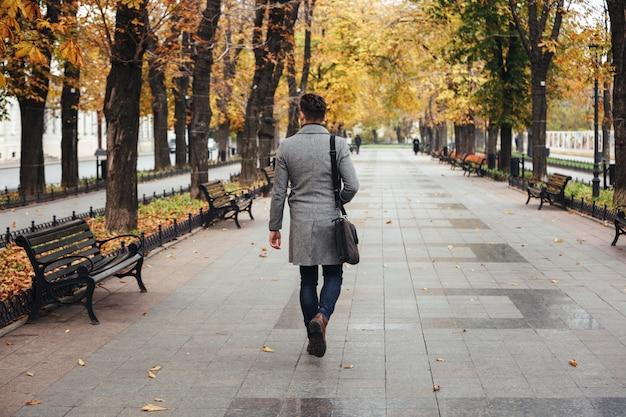 Retrato de la parte posterior del joven con estilo en abrigo con bolsa paseando en el parque de la ciudad, mirando árboles coloridos