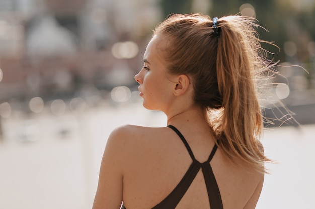 Retrato de la parte posterior de la mujer europea en ropa deportiva en buenos días soleados