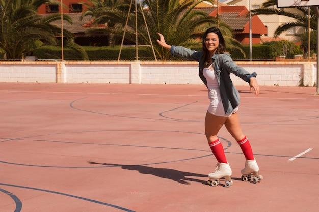 Retrato de una patinadora femenina extendiendo sus brazos patinando en una cancha al aire libre