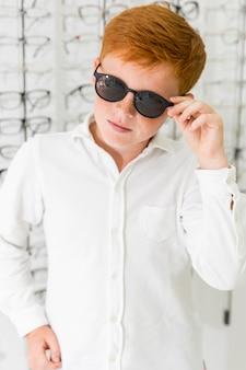 Retrato de pecas boy usando anteojos negros en la tienda de óptica