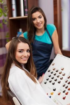 Retrato de peluquero y cliente están listos para teñir el cabello