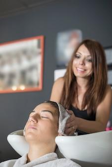 Retrato de un peluquero joven lavando el cabello de un cliente