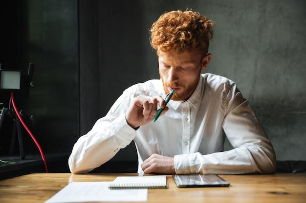 Retrato de pensar joven readhead hombre en camisa blanca, sentado en la mesa de madera con bolígrafo en la boca