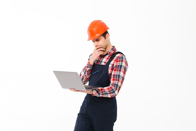 Retrato de un pensativo joven constructor masculino trabajando
