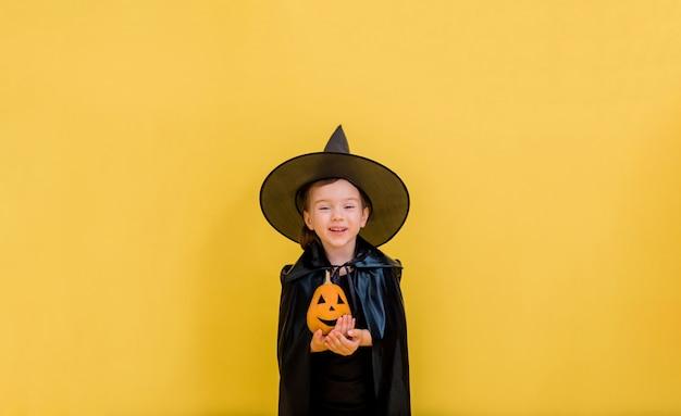 Retrato de una pequeña bruja feliz en un sombrero con una calabaza naranja sobre un amarillo aislado