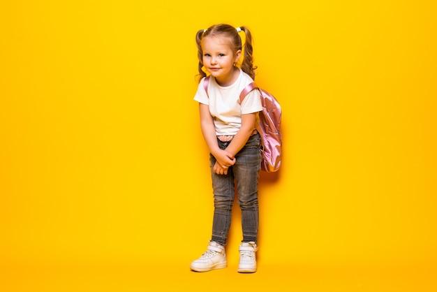 Retrato de una pequeña colegiala sonriente con mochila en la pared amarilla