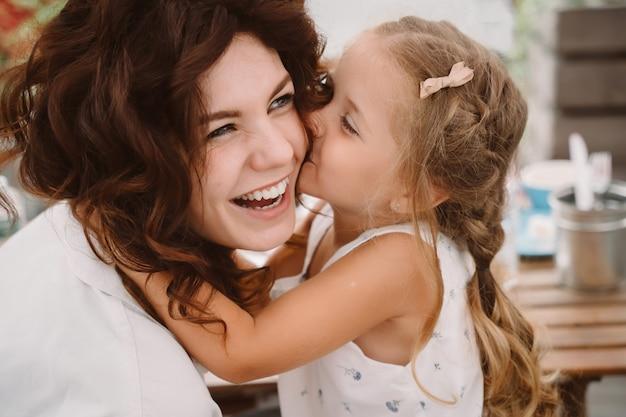 Retrato de pequeña hija besando a su hermosa madre feliz al aire libre