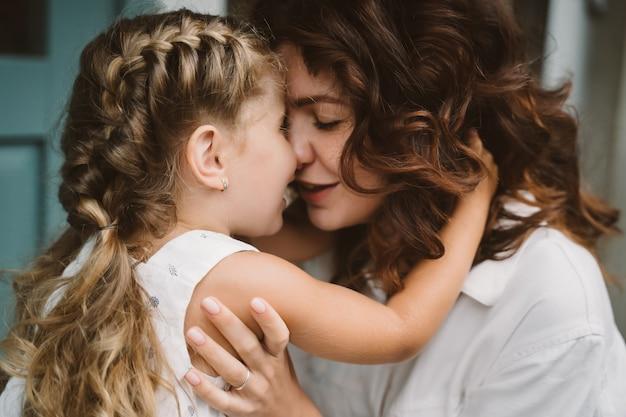 Retrato de pequeña hija besando a su hermosa madre feliz