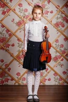 Retrato de la pequeña niña dotada violinista tocando