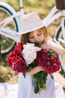 Retrato de una pequeña niña sonriente con un gran ramo de flores en el backgroud verde te