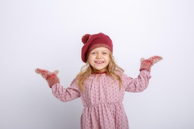 Retrato de una pequeña niña sonriente sobre un fondo gris