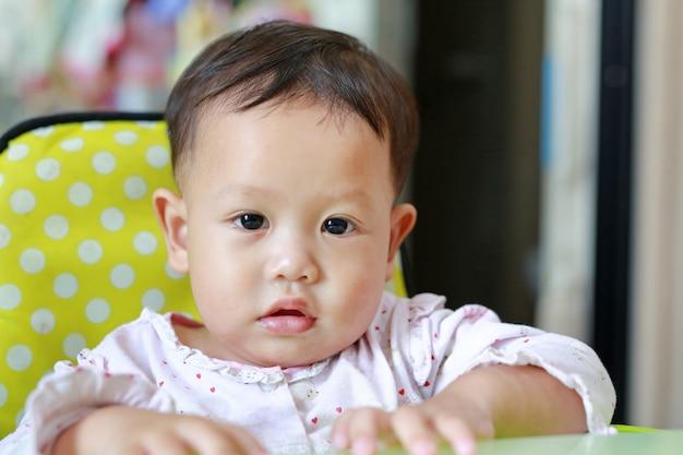 Retrato del pequeño bebé asiático con la nariz que moquea de los mocos. fotografía de cerca.
