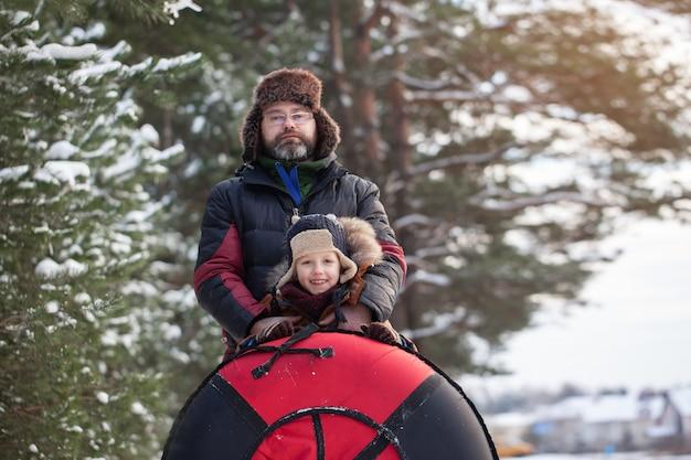 Retrato pequeño bebé y su padre con tubo en día de invierno. diversión al aire libre para las vacaciones familiares de navidad.
