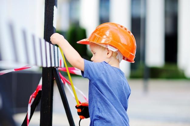Retrato del pequeño constructor lindo en cascos con la regla que trabaja al aire libre