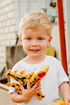 Retrato del pequeño muchacho rubio feliz lindo que sostiene los juguetes del avión y del coche. niño adorable que camina en parque en día asoleado.