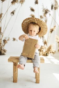 Un retrato de un pequeño niño alegre sobre un fondo blanco con juncos