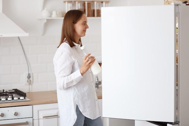 Retrato de perfil de una atractiva mujer de cabello oscuro con camisa blanca, mirando sonriendo dentro de la nevera con emociones positivas, sosteniendo el plato en las manos, posando con cocina en segundo plano.