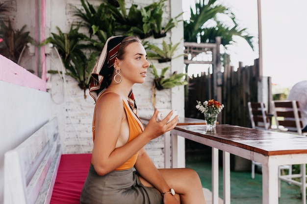 Retrato de perfil de chica guapa atractiva en ropa de verano sentada en un elegante restaurante al aire libre con café con plantas exóticas