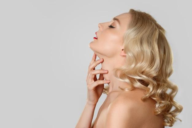 Retrato en perfil de una chica rubia con cabello ondulado tocando su garganta