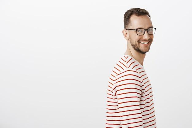 Retrato de perfil de chico caucásico de aspecto amable despreocupado con barba en gafas negras