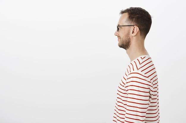 Retrato de perfil de geek feliz contento en gafas negras, sonriendo ampliamente mientras espera en la cola del cine