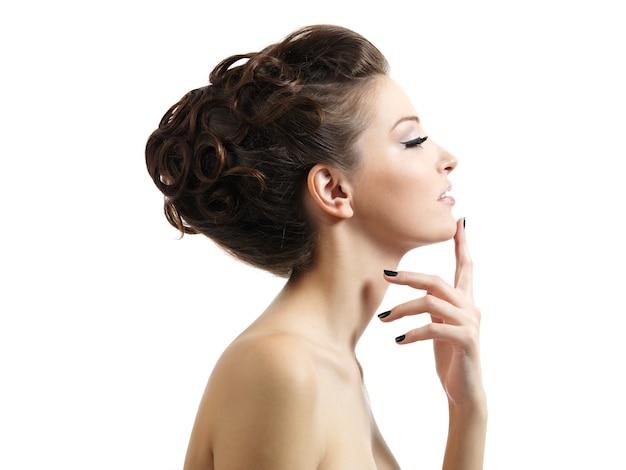 Retrato de perfil de la hermosa joven con peinado rizado en blanco