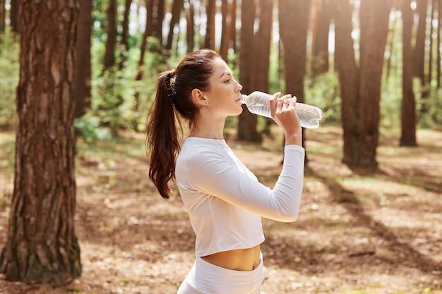 Retrato de perfil de hermosa mujer europea atleta relajada en ropa deportiva blanca de pie, descansando, sosteniendo la botella y bebiendo mientras mira a otro lado