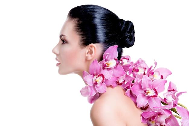 Retrato de perfil de hermosa mujer joven y bonita con piel sana y flores cerca de la cara - aislado en blanco.