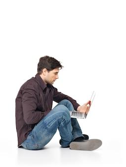 Retrato de perfil de hombre feliz trabajando en equipo portátil en casual aislado en blanco.