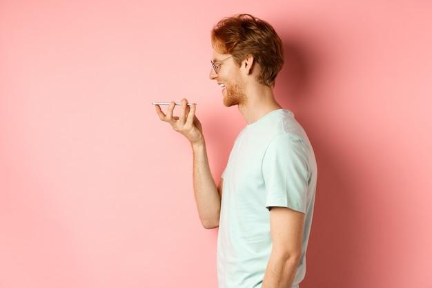 Retrato de perfil joven con cabello rojo, sonriendo complacido mientras graba el mensaje de voz en el teléfono inteligente, hablando con el asistente virtual, de pie sobre fondo rosa.
