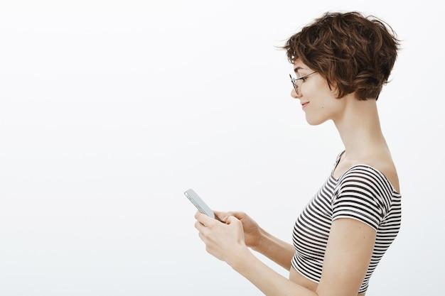 Retrato de perfil de mensaje de texto de mujer joven y elegante en el teléfono móvil, editar perfil en las redes sociales