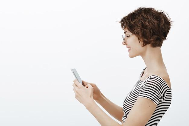 Retrato de perfil de mujer atractiva hipster usando la aplicación de citas, mensajería en el teléfono inteligente o usando la aplicación