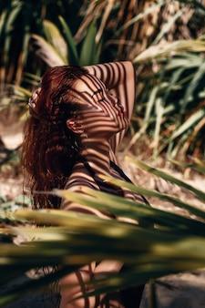 Retrato de perfil: primer plano de una hermosa chica pelirroja posando en las ramas de palmeras.
