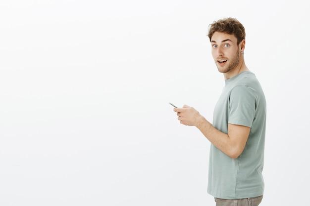 Retrato de perfil de soñador guapo rubio con cerdas, alejándose de la pantalla del teléfono inteligente mientras envía mensajes, esperando café en la cafetería