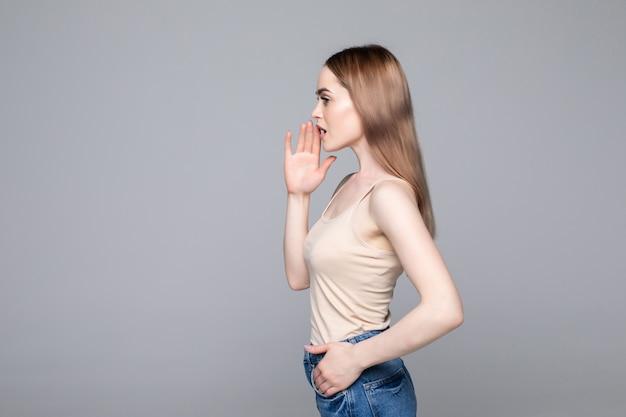 Retrato de perfil de vista lateral de mujer atractiva contando noticias, gritando y sosteniendo la mano cerca de su boca abierta aislada en la pared gris