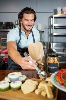 Retrato del personal empacando un pan en una bolsa de papel en el mostrador