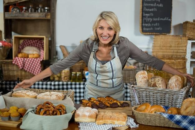 Retrato de personal femenino de pie en el mostrador en la panadería