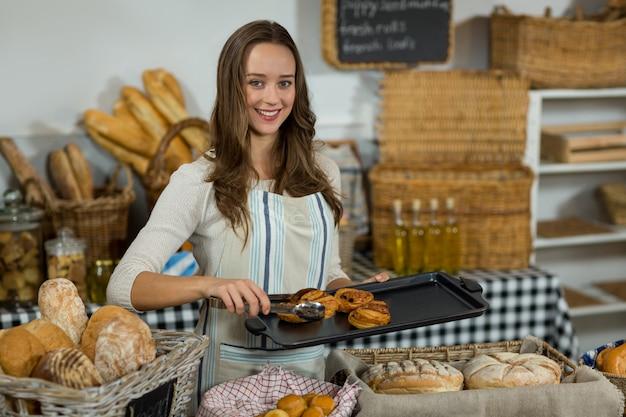 Retrato del personal femenino sonriente colocando croissant en la bandeja en el mostrador
