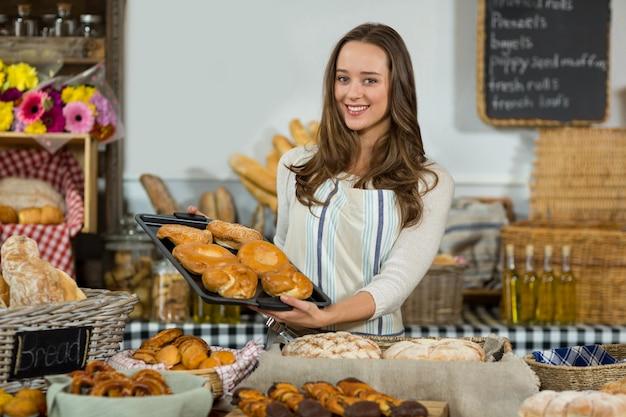 Retrato del personal femenino sonriente que sostiene la bandeja de panes en el mostrador