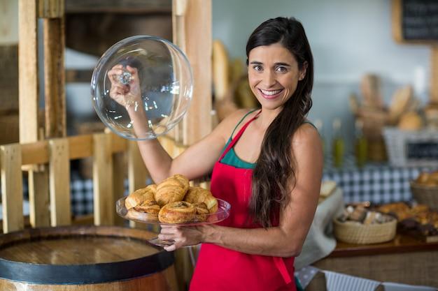 Retrato de personal femenino sonriente sosteniendo una bandeja de bocadillos en el mostrador