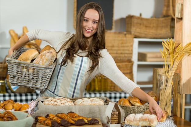 Retrato de personal femenino sonriente sosteniendo panes en canasta de mimbre en el mostrador