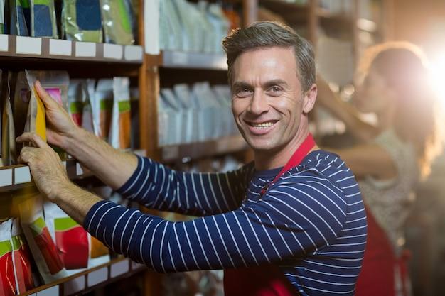 Retrato del personal masculino organizando artículos de supermercado en el estante