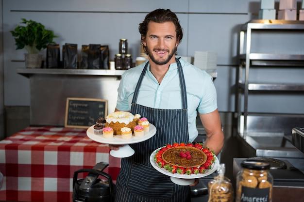 Retrato de personal masculino sosteniendo el postre en el soporte de la torta en el mostrador