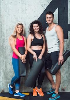 Retrato de personas felices con colchoneta de ejercicios.