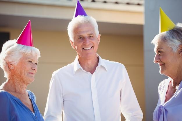 Retrato de personas mayores sonriendo con sombreros de fiesta en la cabeza