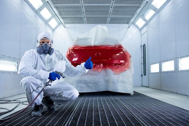 Retrato de pintor de coches profesional con ropa protectora y máscara sosteniendo los pulgares hacia arriba y de pie junto al automóvil en la cámara de pintura.