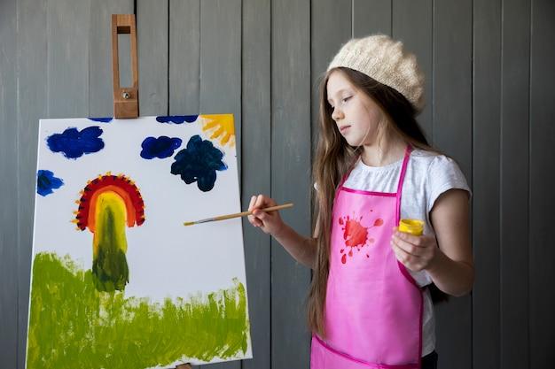Retrato de una pintura linda de la muchacha en el caballete con la brocha