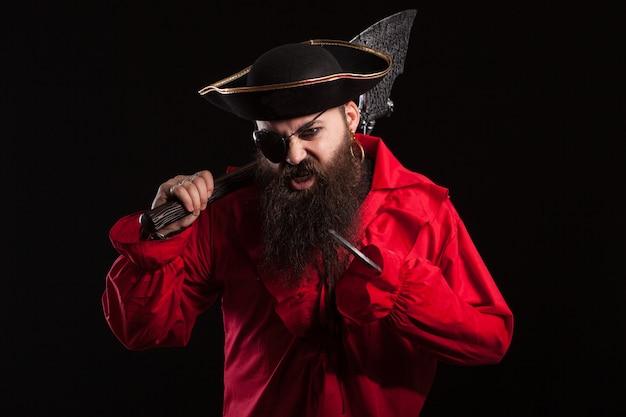 Retrato de un pirata barbudo medieval sobre fondo negro. hombre pirata de expresión agresiva y seria.