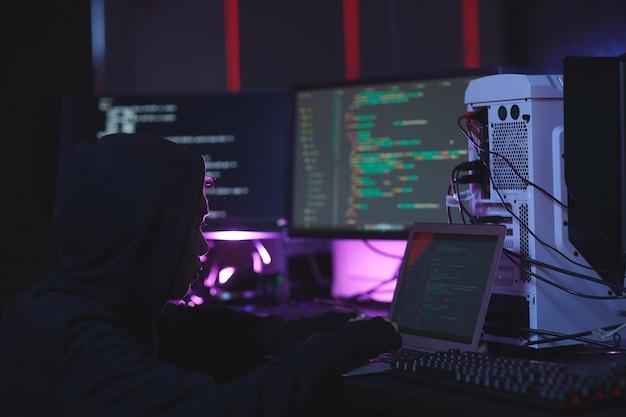 Retrato de pirata informático irreconocible utilizando equipo informático con código de programación en pantallas en una habitación oscura, concepto de seguridad cibernética, espacio de copia